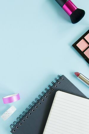 A lipstick, blush, brush, notes, colorful scotch tape on the blue background. Copy space.