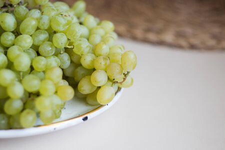 White grape on a white plate. on tha table. Copy space. Banco de Imagens