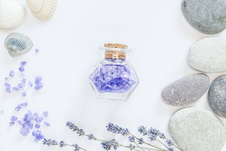 Flowers of lavender, decorative bottle, sea salts in the bottle, grey seastones, seashells on the white background.