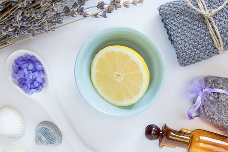 Elements for relaxing and spa. Flowers of lavender, yellow lemon, decorative bottles, grey terry towel, lavender sea salts, seastones and seashells on the white background. Top view.