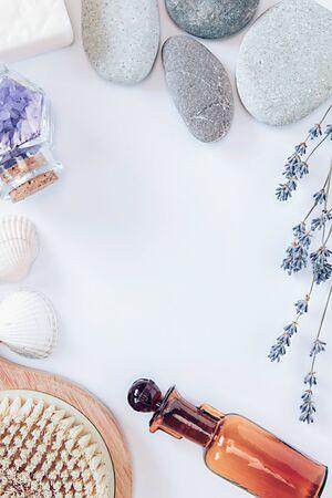 Flowers of lavender, white soap, decorative bottle, brush for massage, sea salts in the bottle, seastones, seashells on the white background.