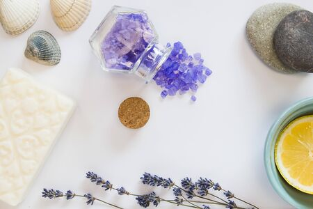 Flowers of lavender, white soap, decorative bottle, a piece of lemon, sea salts in the bottle, seastones, seashells on the white background. Banco de Imagens