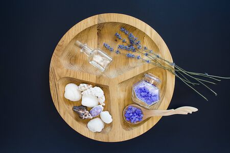 Seshels,violet seasalt, seastones, decorative bottles on the wooden round form on the black background. Top view. Spa and relaxing image.