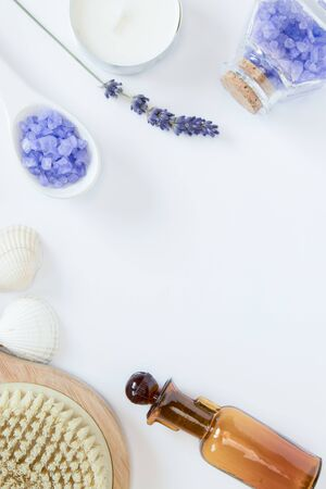 Flowers of lavender, white soap, candle, decorative bottles, brush for massage, sea salts, seashells on the white background. Relaxing concept. Banco de Imagens