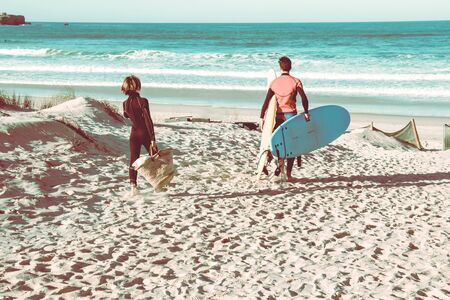 Dad and son with a boards for surfing go to the waves. Banco de Imagens