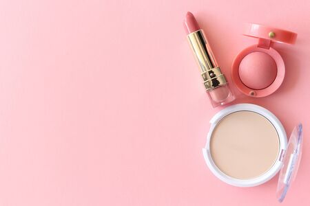 Lipstick, blush, powder, pink. Beautiful concept for spring time. Lipstick, blush and powder on a pastel pink background.
