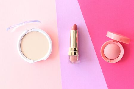 Spring background. Lipstick, beige powder, pink blush on multicolored bright background. Flat lay style.