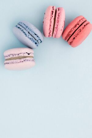 Blue, pink, fresh, sweet, macaroons, flat lay. Fresh macaroons on the blue background. French cake. Top view. Flat lay. Spring concept.