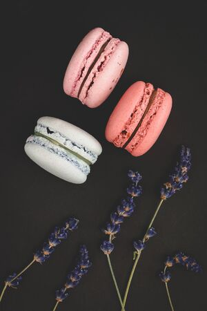 Macaroons, lavender, color, dark. Sweet macaroons on a dark background with flowers of a lavender. Dark background. Spring concept.