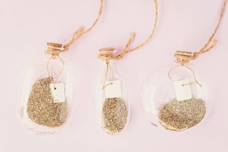 Place for text. Magic background. Decor, bottles, glitter, pink, gold. Three decorative bottles with gold glitter. Spring concept.