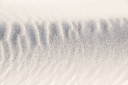 Background, sand, light, beige, wave, reflect, shadow, summer. Beautiful patterns on sand of dune. Close-up. Summer concept. Banco de Imagens