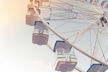 Background with sky, ferris wheel. Ferris wheel and piece sunlight. Vintage style. Close-up. Banco de Imagens