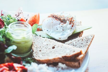 Best breakfast. A plate of breakfast with poached egg, toast, avocado, tomato, salad, green sauce.
