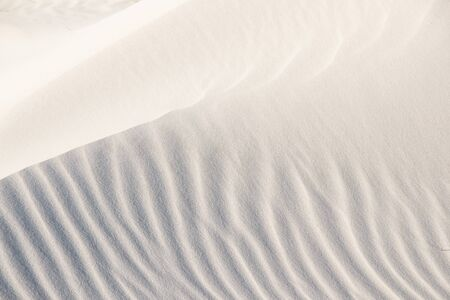 Beautiful beach background. Sand, wave, reflect, shadow, light, beige. Patterns in sand of dune like ruffle in water. Banco de Imagens