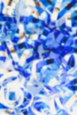 Blurred background. Festive background with sparkling blue and silver confetti. Festive concept. Blue and silver.
