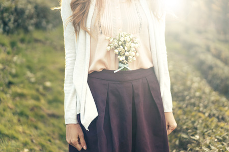 Bouquet of flowers of snowdrops are inserted into the belt of the skirt of a cute woman, funny style