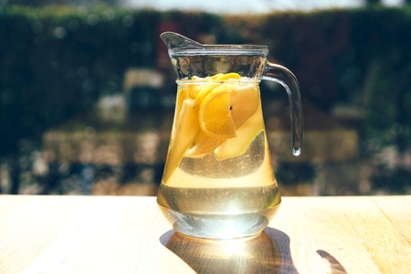 Lemonade in a glass decanter on a hot sunny summer day on the table Imagens