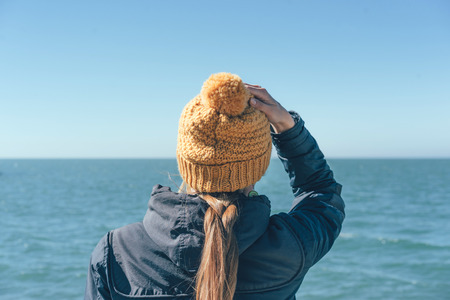The girl the blonde in a yellow warm hat looks at the sea, windy weather