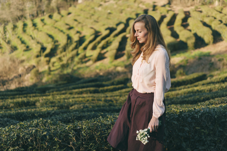 Young woman with long red hair walking along the greenery on a tea plantation in a beautiful dress and with a bouquet of flowers, a gentle bride on the background of a sunny landscape