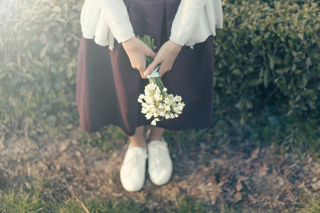 Hipster woman with a bouquet of snowdrops on the background of a natural parkland. 版權商用圖片