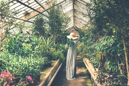 Female figure in a straw hat and a long dress receding back into the depths of a tropical orangery.