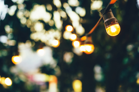 Closeup of light bulbs on the street garland, summer cozy background. Copy space.
