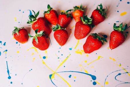 Bright red ripe sweet strawberries on a painted background, summer flat lay, copy space for text, juicy concept. Banco de Imagens