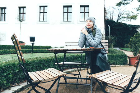Young woman at a table outside in the courtyard of a cafe on a winter day. Tourist part of the city of Prague