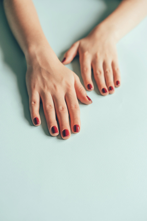 Summer trendy manicure red cherry color, bright stylish nail polish, beautiful well-groomed female hands close-up. 版權商用圖片