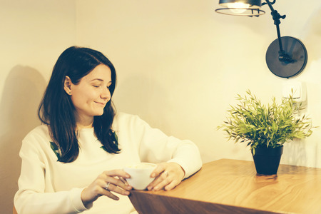 smiling brunette hipster girl at a table in a cozy cafe drinking coffee from a white mug, lighting from a lamp and a potted plant add comfort