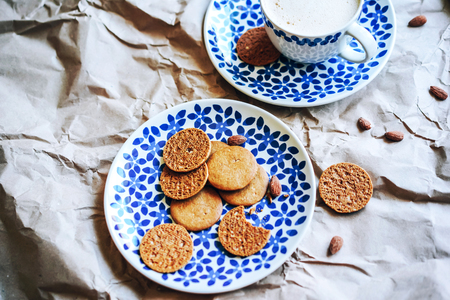 Beautiful ceramic crockery with simim ornament, cookies and coffee for breakfast on a background of crumpled paper.