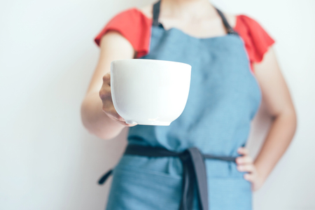 Closeup of female hand holding a big white mug, mock up for text.