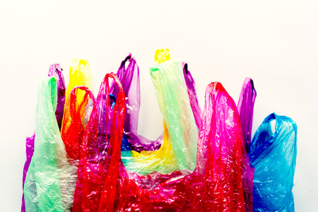 Many multicolored plastic disposable bags, environmental protection concept, bright acid colors