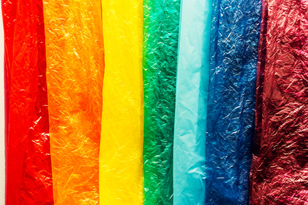Bright plastic bags with a crumpled texture are laid out in order of the colors of the rainbow, a creative idea, a symbol of environmental concern.