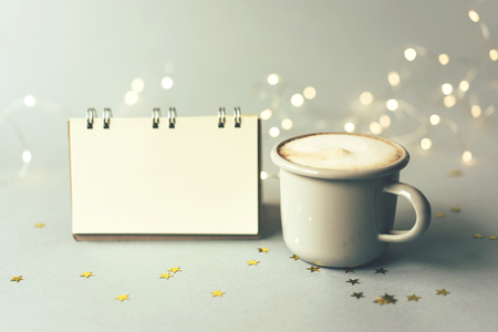 Metal gray coffee mug and blank notepad, bokeh of christmas garland on pastel background.