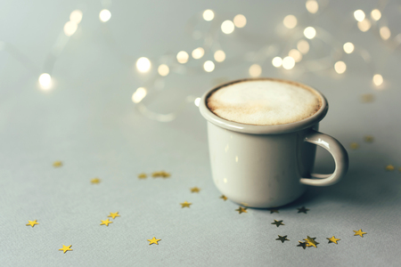 Gray metal mug with coffee, golden stars and bokeh,  copy space for text. Imagens