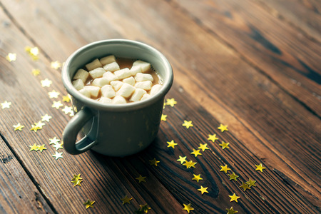 Gray mug with cocoa and marshmallows on a wooden background covered with gold stars, copy space for text.