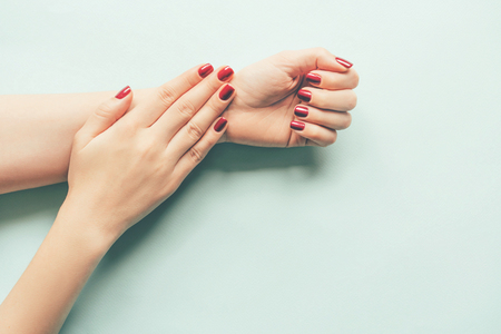 Beautiful female hands with bright red summer manicure on a blue pastel background, a place for text.