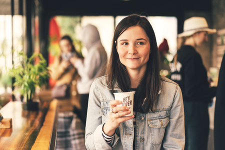 Authentic beautiful happy brunette girl with freckles in a noisy populous coffee shop, holding a paper cup with coffee, smiling. A community of interesting young people, modern life in a big city Imagens
