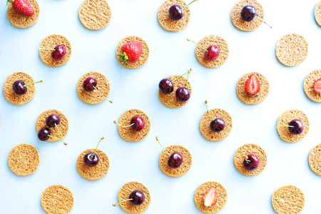 Seamless summer pattern, flat lay with repeating biscuits from cookies and strawberries and cherries.