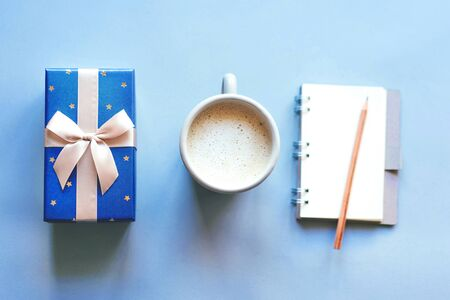 simple layout, top view of a gift box, a mug of coffee and a notebook, conceptual set on a blue background