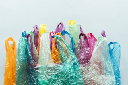 A bunch of disposable plastic multi-colored packages lie on a gray plane, a conceptual background on nature conservation with space for text.