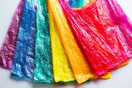 Several different colored plastic bags used on the gray surface are laid out in rainbow colors, a modern environmental concept. Stock Photo