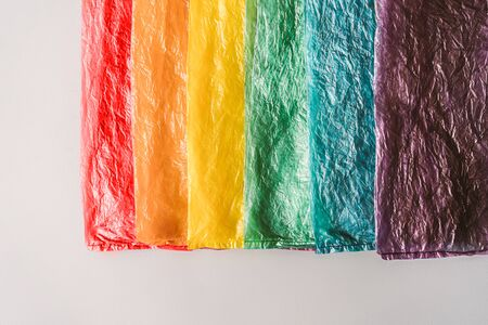 Plastic bags in a row by the colors of the rainbow on grey background. Stock Photo