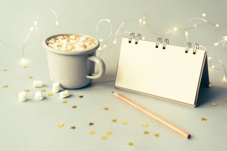 Notepad for the wish list, a cup of coffee and a pencil for writing, bokeh of flashlights in the background and golden stars on the front.