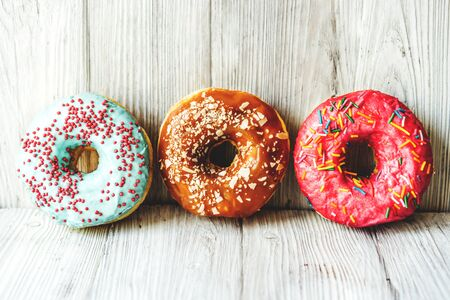 Three fresh delicious sweet donuts in colored glaze on a rustic wooden white background