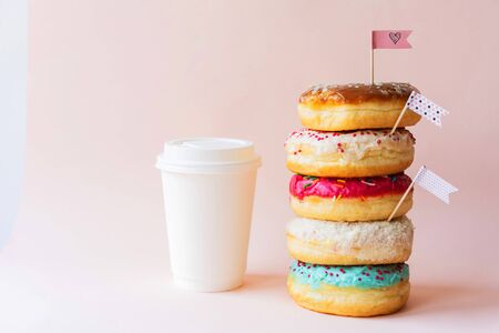 The colored glazed appetizing donuts are assembled in a tower and decorated with flag-shaped toppers, the paper cup is ideally white as a mock-up for text. Pink background with copy space.