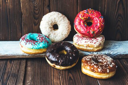 Assorted glazed appetizing donuts on a dark wooden background. Imagens