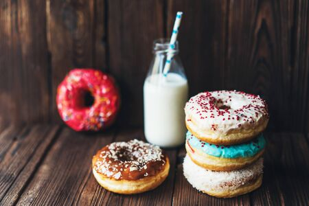 Assorted glazed appetizing donuts and a bottle of milk on a dark wooden rustic background.