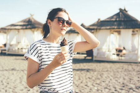 Brunette hipster girl in a striped T-shirt and sunglasses on a hot, sultry day on the beach with tents in her hands holding ice cream, lifestyle womans portrait. Banco de Imagens